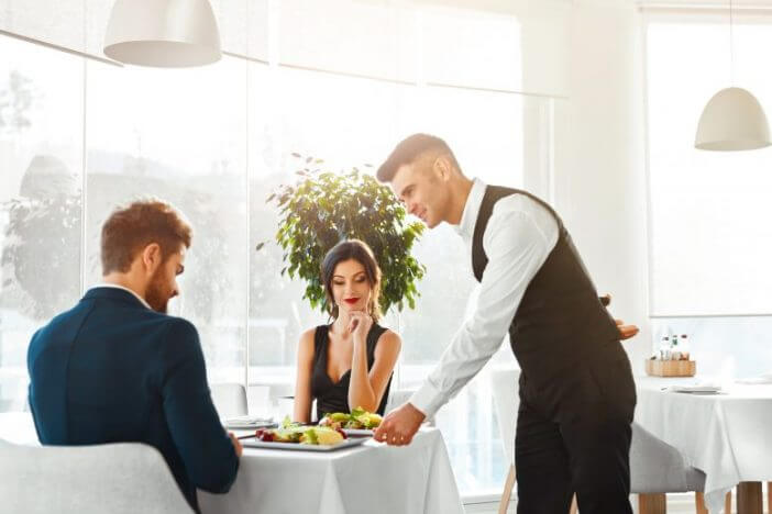 Waiter serving food to couple