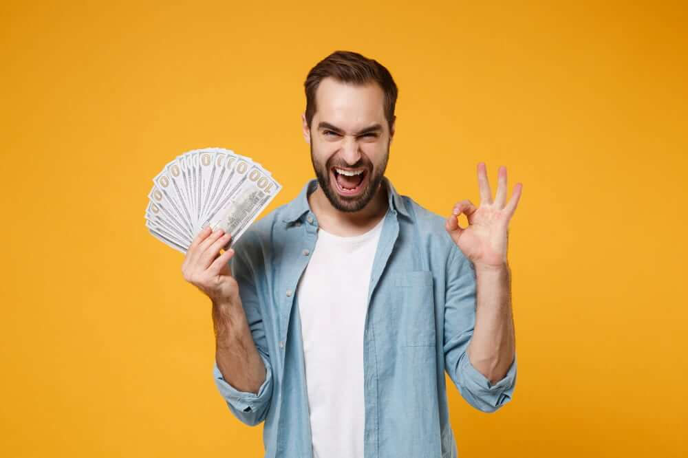 Man smiling holding cash from winning the lottery